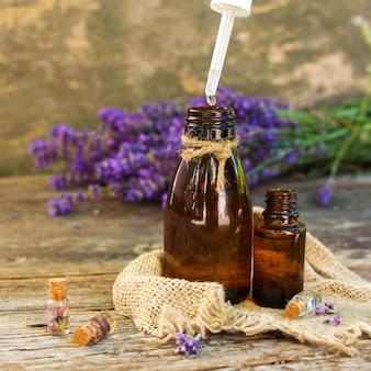 Olio di lavanda in bottiglie diverse su fondo di legno.