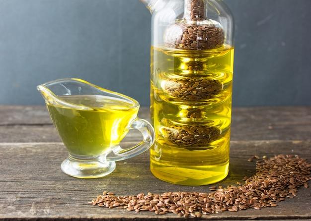 Olio di lino con semi di lino su fondo di legno