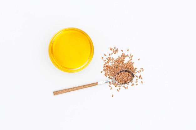 Olio di lino e semi di lino in un cucchiaio isolato su sfondo bianco.