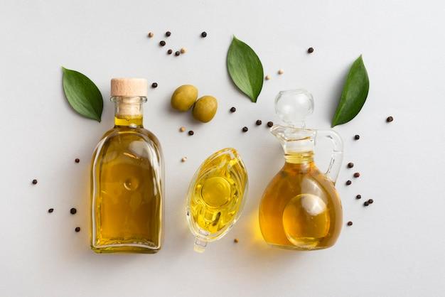 Olio di olive su tavoli con foglie e olive