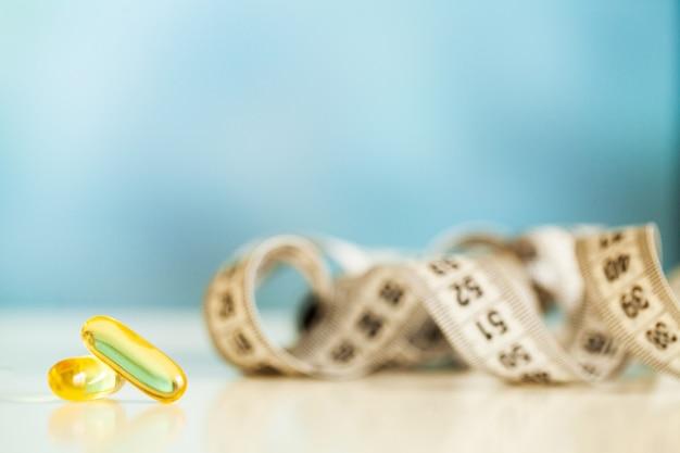 Olio di pesce in capsule gialle omega 3 e nastro di misurazione