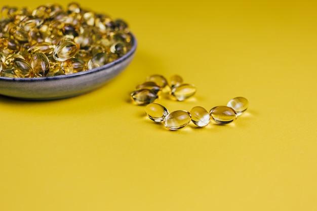 Olio di pesce in capsule su giallo