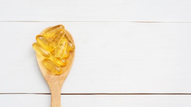 Olio di pesce su un cucchiaio di legno e tavolo in legno bianco.