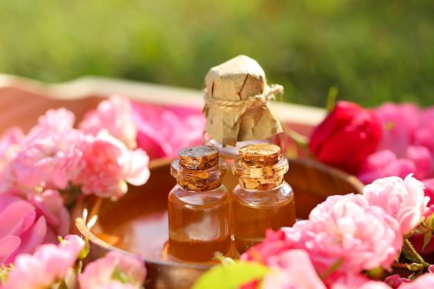 Olio di rose. spa set olio di petali di rosa, acqua di rose in bottiglia di vetro. olio di rose naturale in bottiglie di vetro e rose rosa in un vassoio di legno. concetto di massaggio, aromaterapia e cosmetici biologici