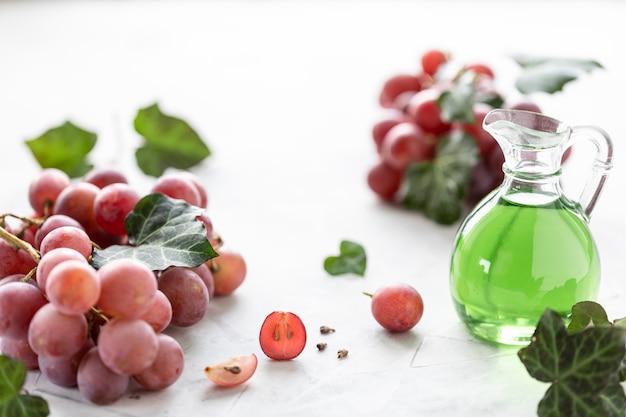 Olio di semi d'uva in una bottiglia di vetro con un grappolo d'uva.