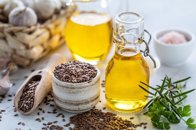 Olio di semi di lino in una bottiglia e ciotola in ceramica con semi di lino marrone e cucchiaio di legno