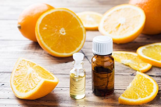 Olio essenziale arancione in bottiglia, fette di frutta fresca su fondo di legno. fragranze naturali
