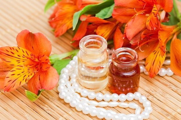 Olio essenziale aromatico in piccole bottiglie di vetro, fiori di alstroemeria e perle di perle