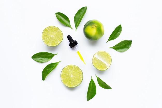 Olio essenziale con calce e foglie isolate su bianco