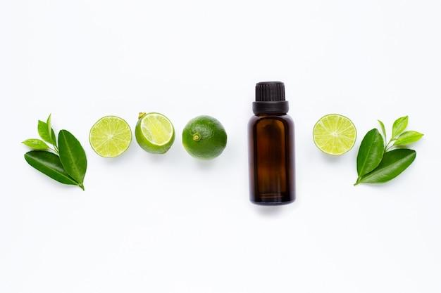 Olio essenziale con calce e foglie isolate su bianco.