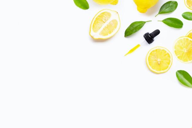 Olio essenziale con il limone e le foglie verdi freschi su bianco
