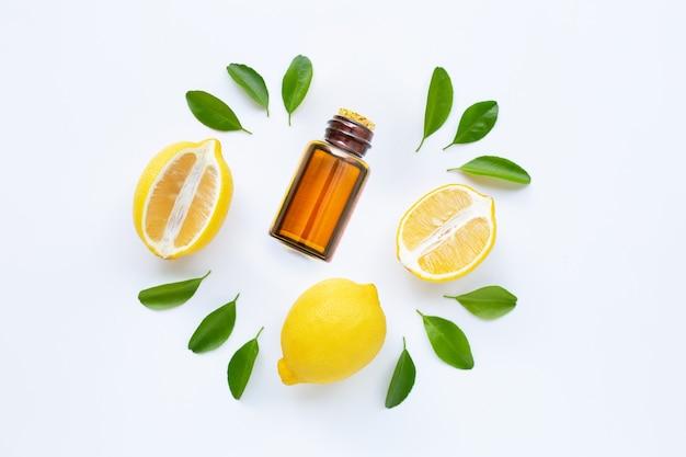 Olio essenziale con limone e fette isolati su bianco