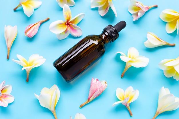 Olio essenziale con plumeria o fiore di frangipane sul blu.