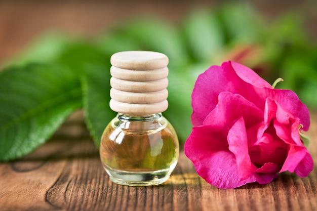 Olio essenziale del cinorrodo in bottiglia di vetro su fondo di legno.