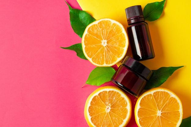 Olio essenziale di agrumi agrumi affettati e bottiglie dell'aroma sul rosa