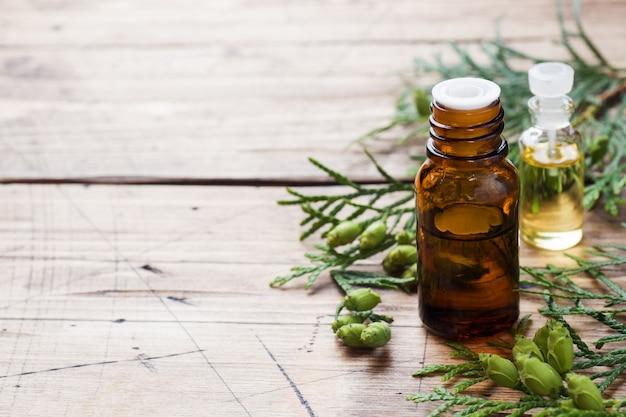 Olio essenziale di aroma di thuja in un barattolo di vetro su superficie di legno