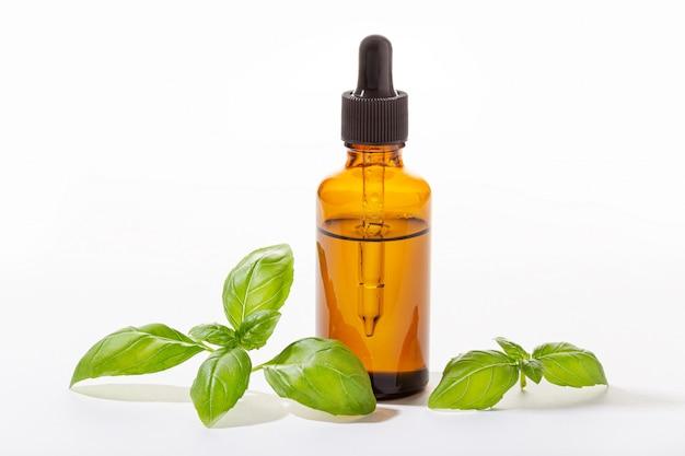 Olio essenziale di basilico isolato su bianco. olio di basilico per la cura della pelle, aromaterapia e medicina naturale