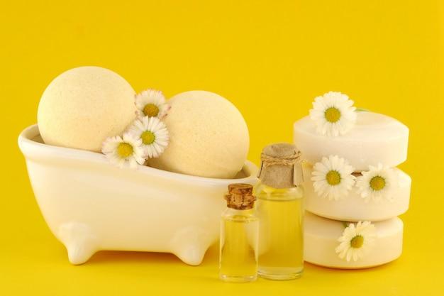 Olio essenziale di camomilla, sapone e bombe da bagno su giallo