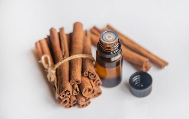Olio essenziale di cannella in una bottiglietta. messa a fuoco selettiva.