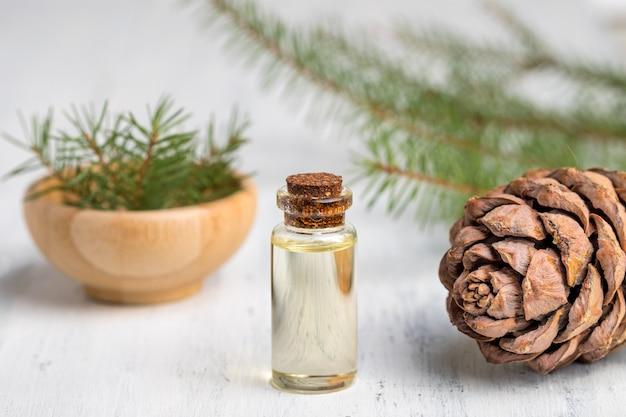 Olio essenziale di cedro in una bottiglia di vetro. focalizzazione morbida. fondo in legno bianco