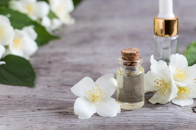 Olio essenziale di gelsomino. massaggi l'olio con i fiori del gelsomino su un fondo di legno
