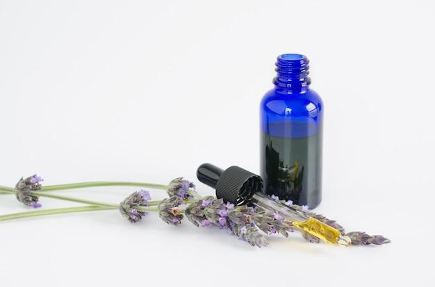 Olio essenziale di lavanda fiori e bottiglia con pipetta su superficie bianca
