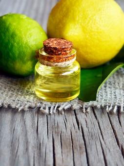 Olio essenziale di lime in una bottiglia di vetro con frutta fresca. olio di limone per spa, aromaterapia e cura del corpo. olio di limone estratto. messa a fuoco selettiva.