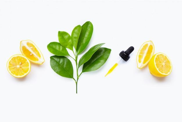 Olio essenziale di limone e frutti di limone su bianco