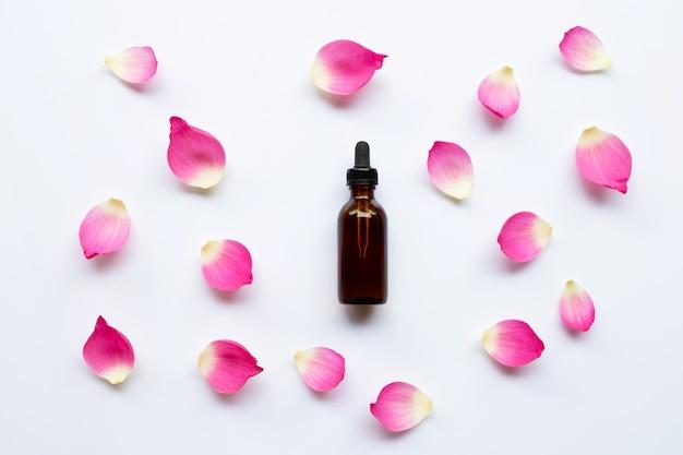 Olio essenziale di loto con petali di loto su sfondo bianco.