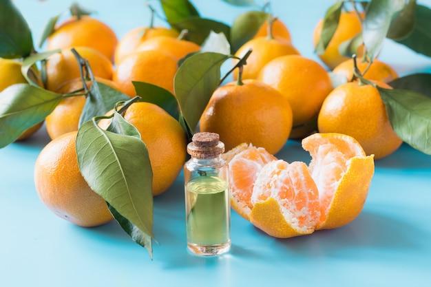 Olio essenziale di mandarino arancio in bottiglia di vetro sul blu