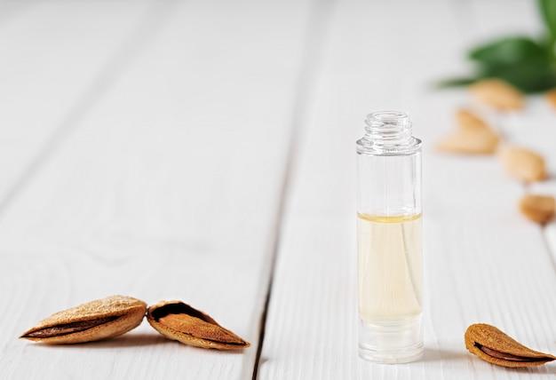 Olio essenziale di mandorle naturali con mandorle e foglie verdi