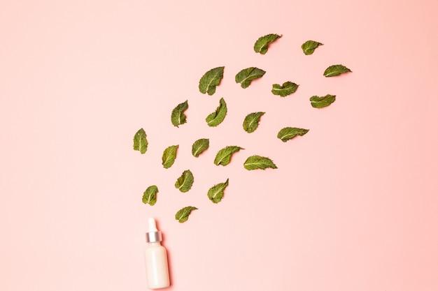 Olio essenziale di menta naturale in una bottiglia di vetro con foglie di menta fresca