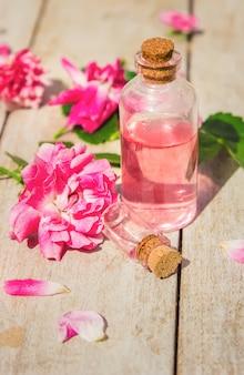 Olio essenziale di rosa su sfondo chiaro. messa a fuoco selettiva