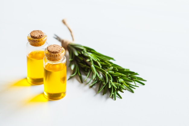 Olio essenziale di rosmarino in bottiglie di vetro, fondo bianco, spazio della copia.