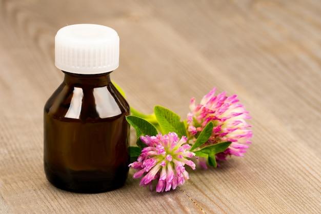 Olio essenziale di trifoglio in bottiglia di vetro marrone sul tavolo rustico in legno