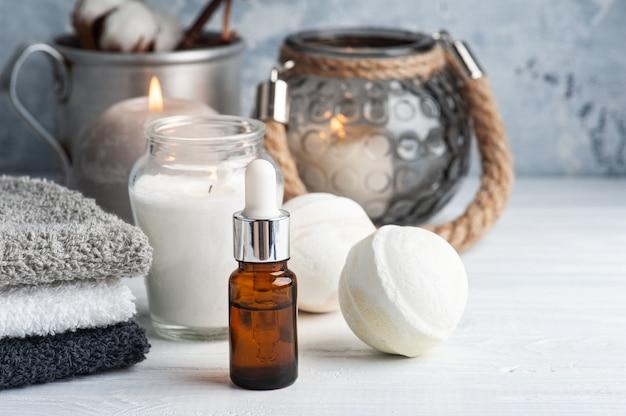 Olio essenziale e bombe da bagno nella spa allestita con fiori secchi e candele accese