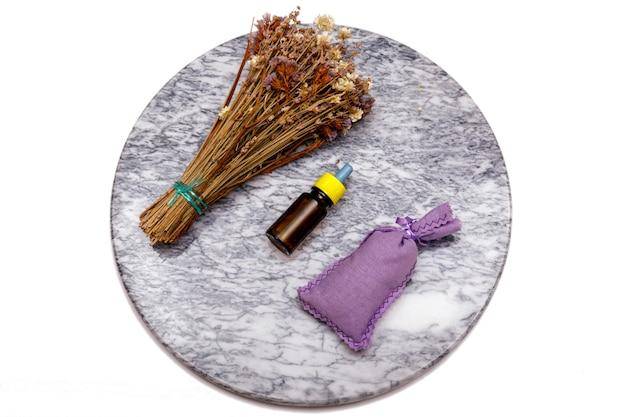 Olio essenziale e fiori di lavanda. selezione di olio essenziale sul tavolo di marmo con varie erbe e fiori biologici