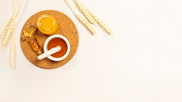 Olio essenziale e miele su sughero marrone con spighe di grano su sfondo bianco