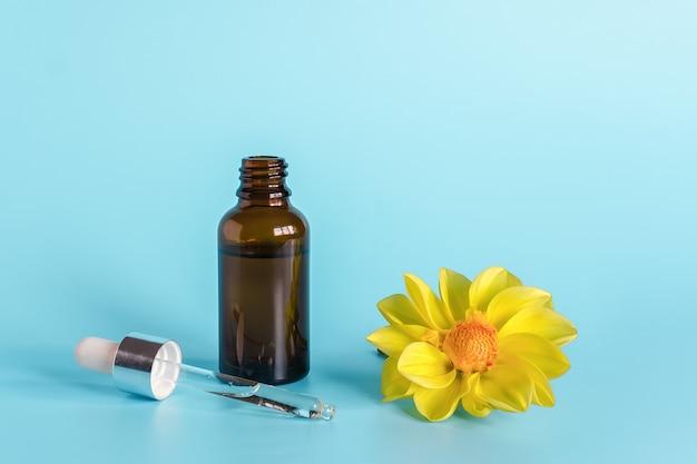 Olio essenziale in flacone contagocce marrone aperto con pipetta in vetro disteso e fiore giallo. cosmetici biologici naturali di concetto