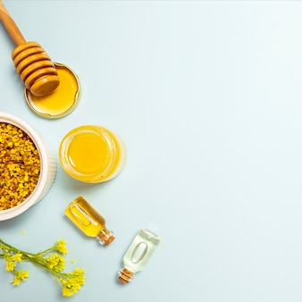 Olio essenziale; polline d'api e miele con fiori freschi gialli su sfondo blu