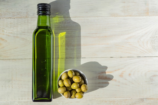Olio extra vergine di oliva in bottiglia verde e olive verdi fresche sul tavolo di legno.