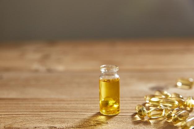 Olio in una bottiglia di vetro e capsule di olio su una superficie di legno