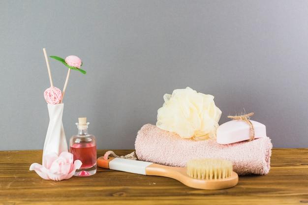 Olio; spazzola; asciugamano; luffa e sapone sul ripiano del tavolo in legno
