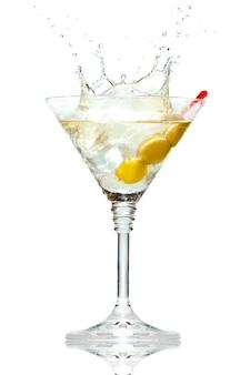 Oliva che spruzza sul vetro del martini isolato su bianco