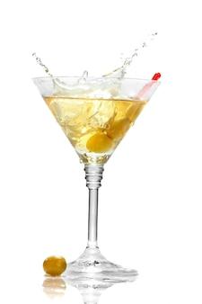 Oliva che spruzza sul vetro del martini isolato
