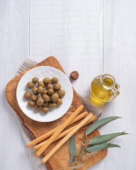 Olive amichevoli di eco naturale maturo con olio d'oliva in una bottiglia e grissini su un fondo di legno bianco