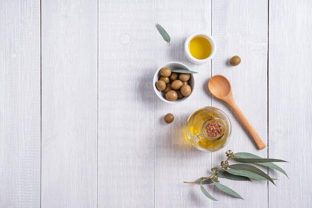 Olive amichevoli di eco naturale maturo con olio d'oliva in una bottiglia su un fondo di legno bianco