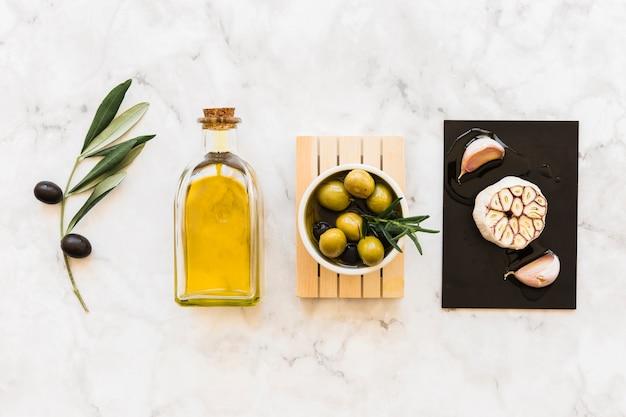 Olive con bottiglia e bulbo di aglio e chiodi di garofano