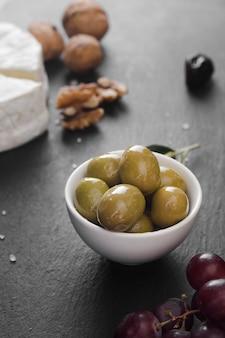 Olive dell'angolo alto e composizione nel formaggio su fondo nero