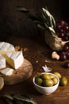 Olive dell'angolo alto e composizione nel formaggio sulla tavola